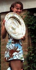 Martina Hingis displays her trophy on Sunday, July 6, the day after defeating Jana Novotna